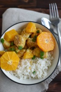 orange chicken on a bed of white rice garnished with fresh orange slices and scallions