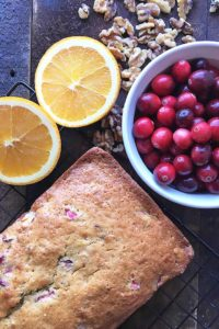 cranberry nut bread next to bowl of cranberries and oranges cut in half