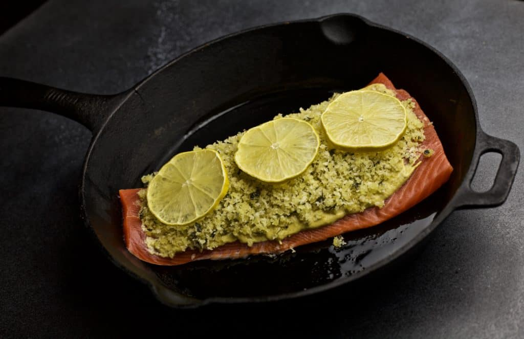 cast iron skillet with salmon filet topping with panko and lemon