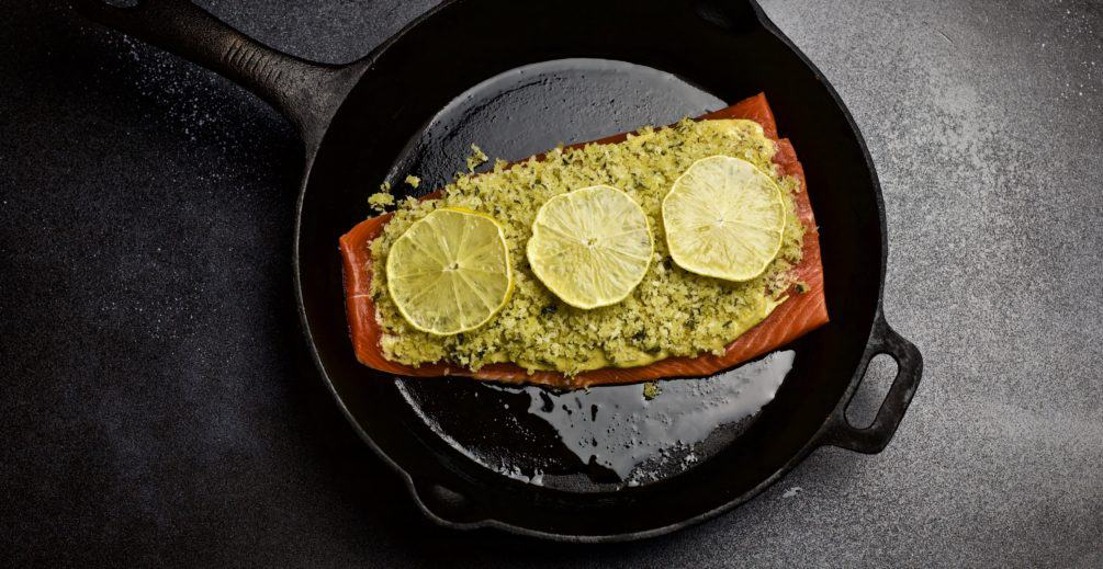 cast iron skillet with baked salmon topped with panko breadcrumbs and lemon
