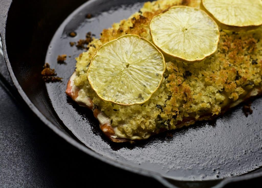 salmon cooked in cast iron skillet topped with fresh lemon slices