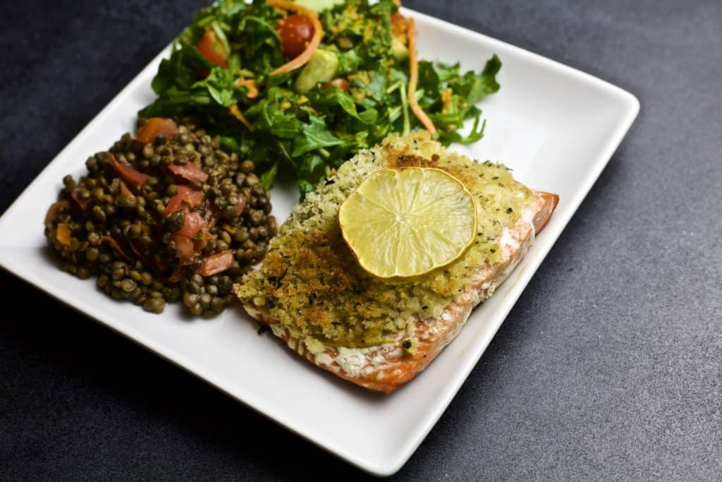 cast iron skillet salmon served with salad and lentils