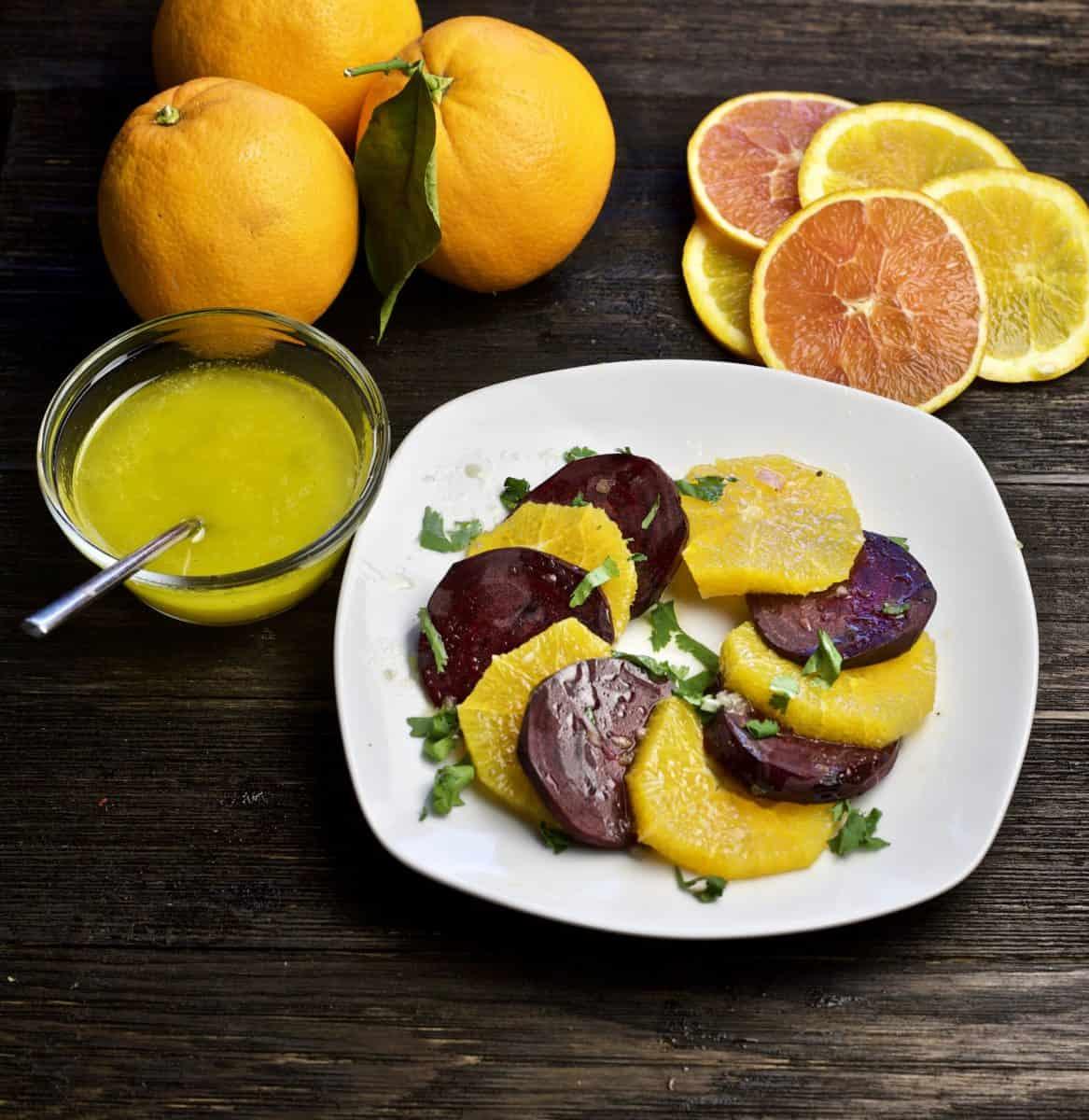 beet and orange salad with citrus vinaigrette on side and sliced oranges in top corner