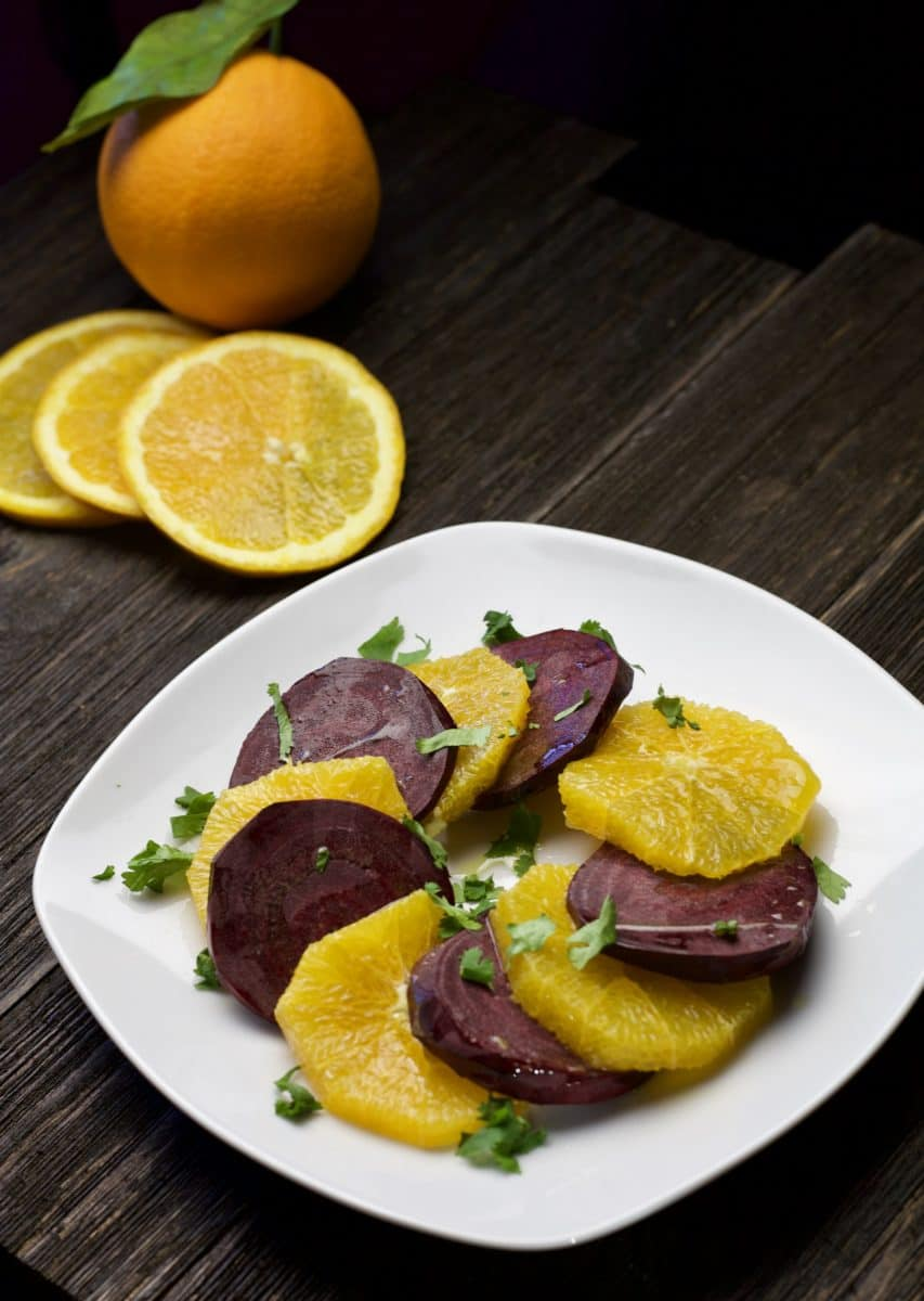 beet and orange salad on white plate with oranges in background