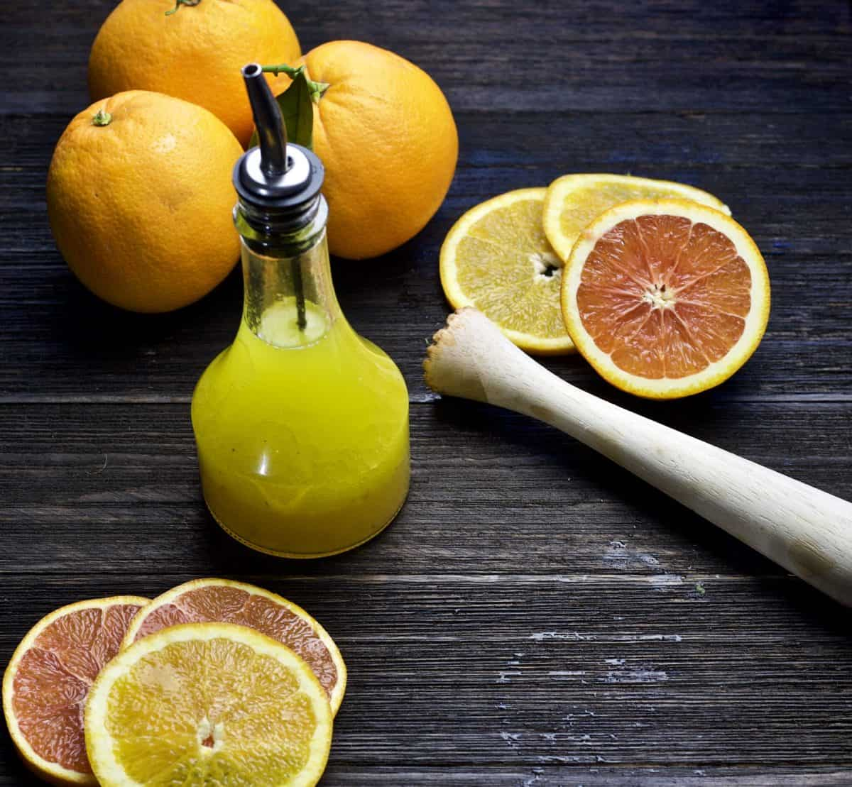 citrus vinaigrette in pour bottle with sliced oranges and juicer surrounding it