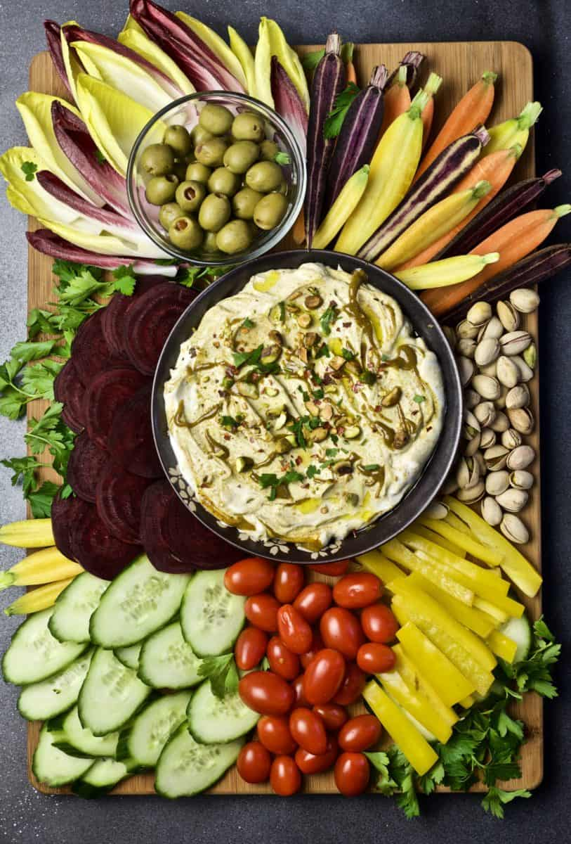 large platter of beets, cucumber slices, cherry tomatoes, endive spreads, rainbow baby carrots, and olives surrounding bowl of pistachio yogurt dip