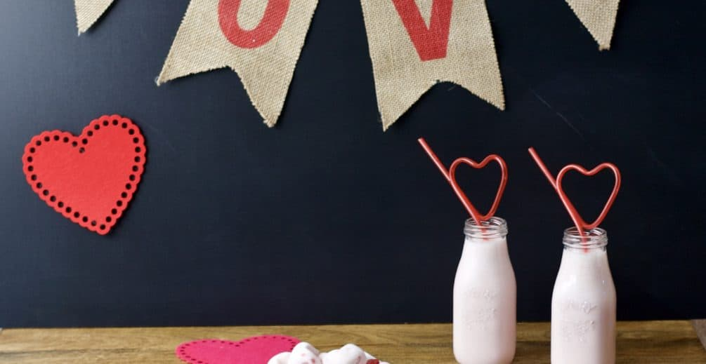 LOVE banner with strawberry smoothie, berry cups and yogurt hearts on holiday decorated table