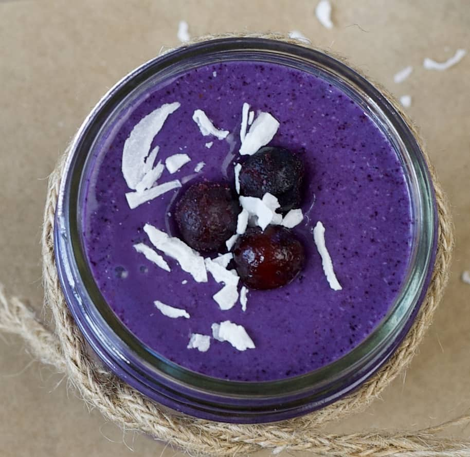 close up of a purple smoothie topped with frozen blueberries and shredded coconut