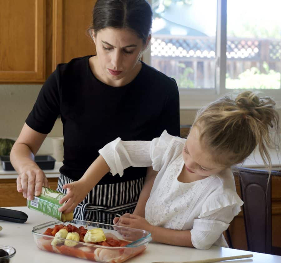 little girl pouring can into pan to bake dinner with mom