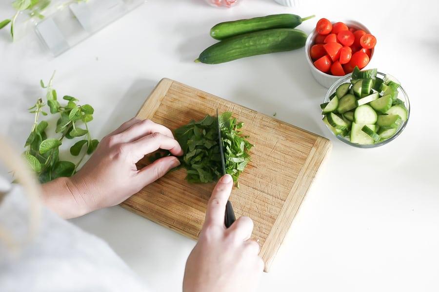 chopping fresh herbs for greek farro salad recipe
