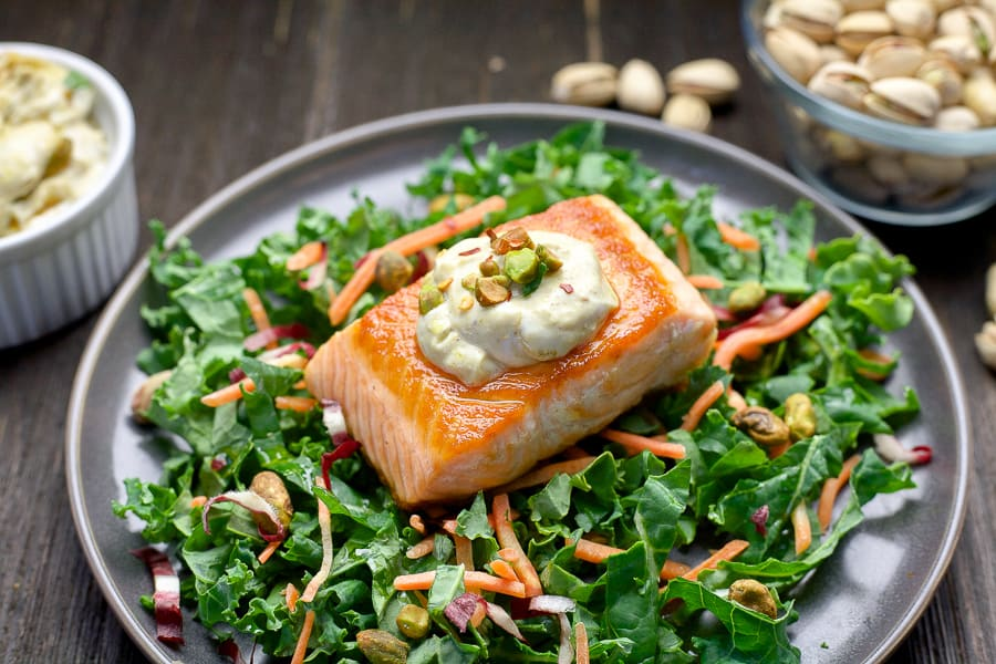 salmon on bed of greens with pistachio sauce